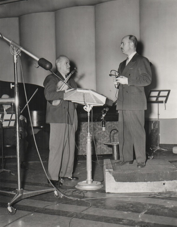 Winston Sharples (right) confers with his violinist.