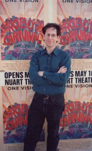 Jerry Beck stands in front of a wild posting of ROBOT CARNIVAL posters  in late April 1991