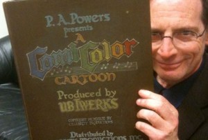 Jerry Beck examines the prop book used as the titles in many of the latter ComiColor cartoons (The book courtesy of, and photo shot by, Mike Van Eaton)