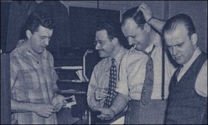 Marty Taras at Famous Studios in a 1945 photograph, with cigarette and hand on his head. (with George Ottioni, Lou Zukor and Pete DeAngel)